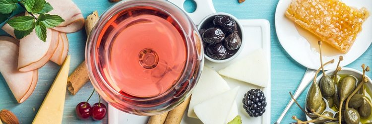 Summer wine snack set. Glass of rose, meat, cheese, olives, honey, bread sticks, nuts, capers and berries with white ceramic board in center, blue wooden background, top view