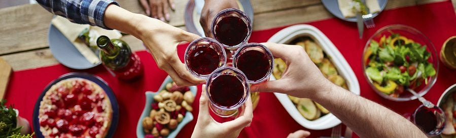 Group of friends toasting with glasses of red wine by festive table