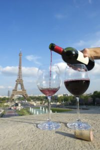 Hand pouring red wine from bottle into glasses in front of romantic view of Eiffel Tower in Paris France