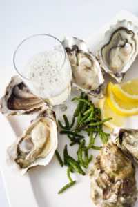 Oysters, lemon, seaweed, champagne glass on plate