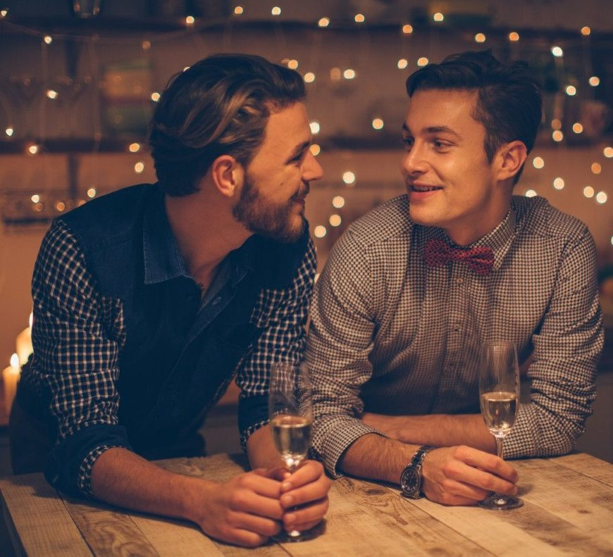 Loving gay couple having romantic date, drinking champagne. Domestic kitchen. Evening scene lit by candle and string lights.