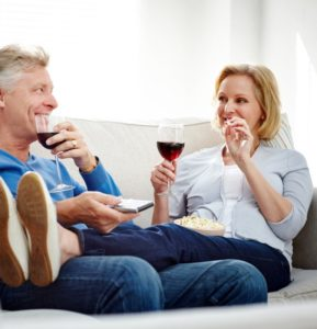 Happy mature couple relaxing together on sofa with popcorn and wine looking at each other while watching television at home