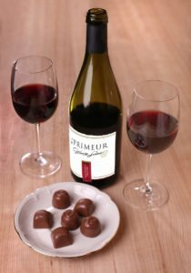 two glasses of red wine chocolate and bottle